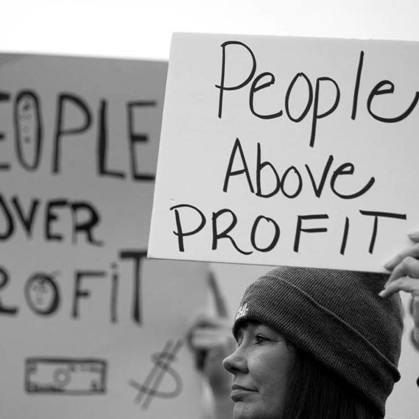 "A woman holding a sign that reads ""People Above Profit"""